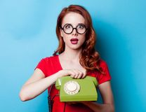 Portrait of young redhead woman with handset Royalty Free Stock Image
