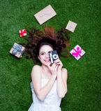 Portrait of a young redhead woman with holiday gifts and camera Royalty Free Stock Images