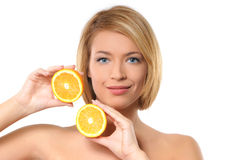 Portrait of a young redhead woman with oranges. Portrait of a young and beautiful redhead woman holding two pieces of a fresh and tasty orange. The image is royalty free stock image