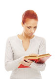 Portrait of a young redhead woman reading a book Stock Photography