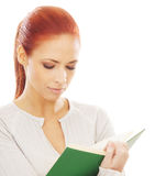 Portrait of a young redhead woman reading a book Stock Photo