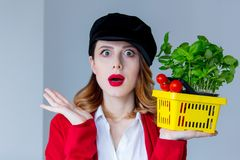 Woman in red cardigan and hat with herbs and tomatoes in yellow Royalty Free Stock Images