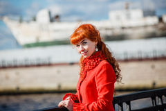 Portrait of young redhead woman in red winter coat Royalty Free Stock Photos