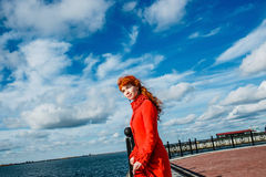 Portrait of young redhead woman in red winter coat Royalty Free Stock Images
