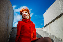 Portrait of young redhead woman in red winter coat Stock Photos