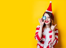 Woman in Santa Claus hat with little alarm clock. Portrait of young redhead woman in Santa Claus hat and striped shirt with little alarm clock on yellow Stock Image
