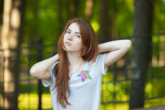 Portrait of a young redhead woman stretch herself outdoor blurry forest park background Stock Photography
