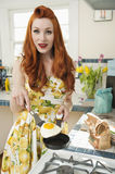 Portrait of a young redheaded woman cooking omelet Royalty Free Stock Image
