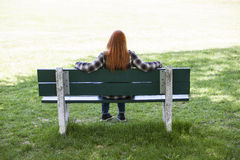 Portrait of young redheaded woman sitting on park bench. Royalty Free Stock Photos