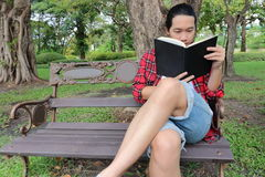 Portrait of young relaxed man  reading a book on the bench in beautiful outdoor park. Royalty Free Stock Photos