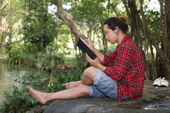 Portrait of young relaxed man in red shirt reading a book in beautiful nature background. Royalty Free Stock Photo