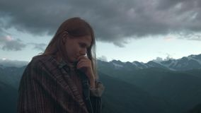 Portrait of a young romantic girl on a background of mountains. A beautiful girl looks at the sunset, behind the snow stock video