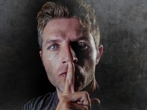 Portrait of young 30s man with finger on his lips in silence and shut up hand gesture warning or threatening not to speak in polit. Close up studio portrait of royalty free stock photos