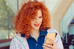 Portrait of young sad annoyed woman, receiving bad sms. On city building background stock image