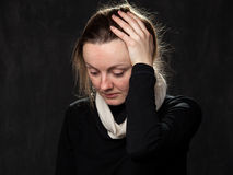 Portrait of a young sad disoriented woman. Grey background Stock Image