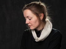 Portrait of a young sad disoriented woman. Looking down, head is half-turned , grey background Royalty Free Stock Photography
