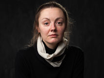 Portrait of a young sad disoriented woman. In white scarf, grey background Stock Image