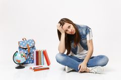 Portrait of young sad exhausted woman student in denim clothes resting forehead on hand, sit near globe backpack school royalty free stock photography