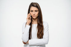 Portrait of young sad girl talking on her phone over white background being upset. Portrait of young sad girl talking on her phone over white background Stock Images