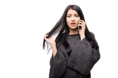 Portrait of young sad girl talking on her phone over white. Background Stock Image