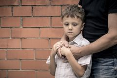 Portrait of young sad little boy and father sitting outdoors at. The day time. Concept of sorrow stock photography