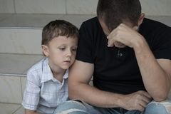 Portrait of young sad little boy and father sitting outdoors at. The day time. Concept of sorrow royalty free stock image