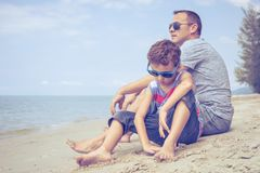 Portrait of young sad little boy and father sitting outdoors at. Portrait of young sad little boy and father sitting outdoors on the beach at the summer day time stock images