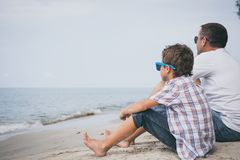 Portrait of young sad little boy and father sitting outdoors at. The day time. Concept of sorrow royalty free stock images