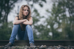 Portrait of young sad ten girl sitting outdoors at the day time. Portrait of young sad ten girl sitting outdoors  on the railway at the day time. Concept of Stock Photo