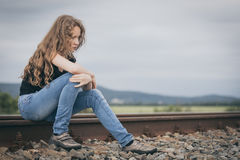 Portrait of young sad ten girl sitting outdoors at the day time. Portrait of young sad ten girl sitting outdoors  on the railway at the day time. Concept of Stock Photos