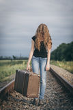 Portrait of young sad ten girl standing with suitcase outdoors a. Portrait of young sad ten girl standing with suitcase outdoors  on the railway at the day time Stock Image