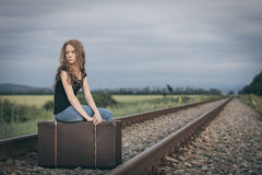 Portrait of young sad ten girl standing with suitcase outdoors a. Portrait of young sad ten girl sitting with suitcase outdoors on the railway at the day time royalty free stock image