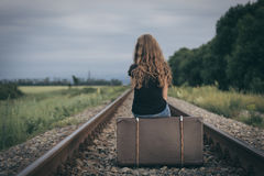 Portrait of young sad ten girl standing with suitcase outdoors a. Portrait of young sad ten girl sitting with suitcase outdoors on the railway at the day time royalty free stock photos