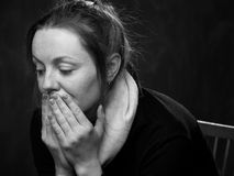 Portrait of a young sad woman. Portrait of a young sad disoriented woman sitting on the chair , grey background Stock Image
