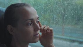 Portrait of young sad woman looking out the wet window, while travelling by bus.