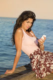 Portrait of young sad woman, receiving bad sms on the beach Stock Photo