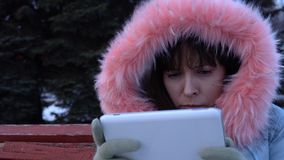 A young woman in a warm jacket uses a digital tablet in the park in the winter. Portrait of a young sad woman uses a digital tablet and sitting on a bench in a stock video footage