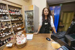 Portrait of young saleswoman standing at cash counter in supermarket Stock Images