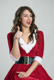 Portrait of young Santa female helper winking with thumbs Royalty Free Stock Photos