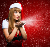 Portrait of a young Santa girl blowing stars Stock Photo