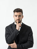 Portrait of young scared man with finger over his lips looking at camera Royalty Free Stock Photos