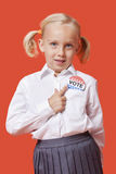 Portrait of a young school girl with vote badge over orange background Stock Images