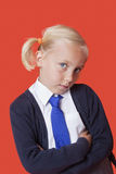 Portrait of a young schoolgirl with arms crossed over orange background Royalty Free Stock Photography