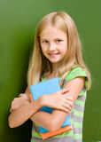 Portrait of young schoolgirl with books near chalkboard Royalty Free Stock Photography
