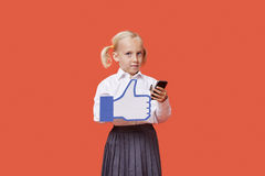 Portrait of a young schoolgirl with cell phone holding fake like button over orange background Royalty Free Stock Photos