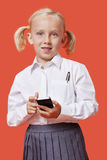 Portrait of a young schoolgirl holding cell phone over blue background Royalty Free Stock Photo