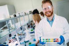 Portrait of young scientist posing in lab. Portrait of young smiling scientist posing in lab Stock Photo