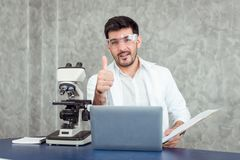 Portrait of young scientist research using microscope in a labor stock image