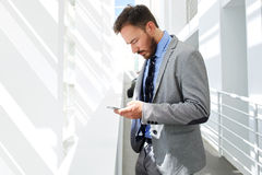 Portrait of a young serious businessman reading text message on his cell telephone while standing in big white corridor Stock Photography