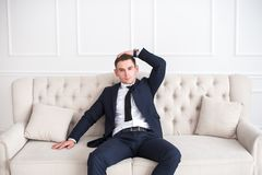 Portrait of a young serious and confident man in a suit sitting on the couch and looking at camera. Model photo Royalty Free Stock Photography